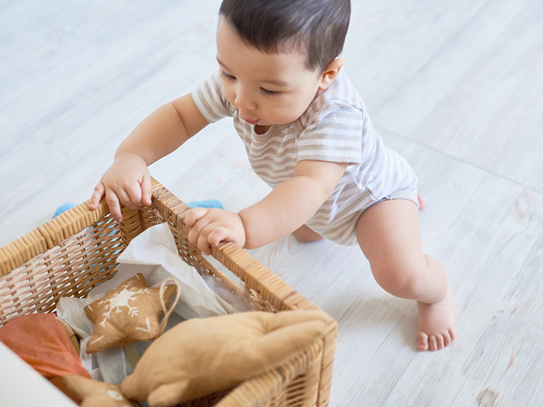 Baby boy looking into wicker basket