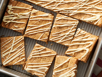 chewy chai-spiced blondie dessert topped with drizzled vanilla icing