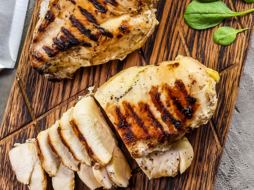 grilled chicken breast on wood cutting board