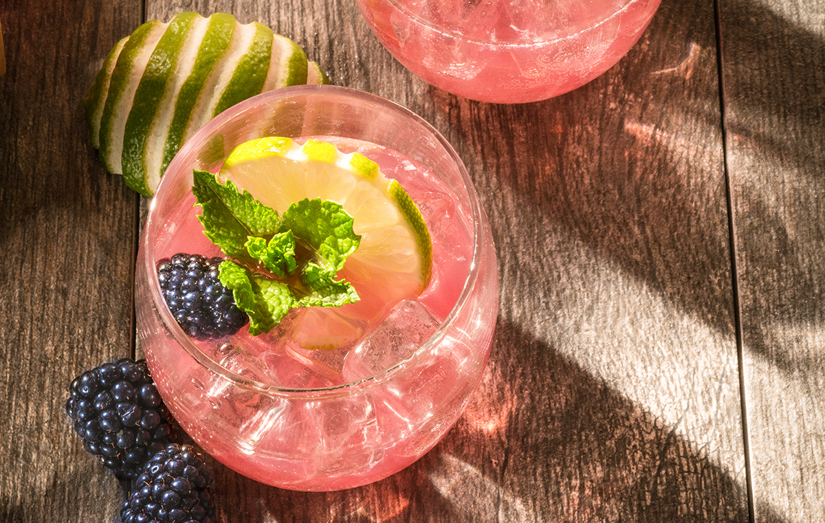 Drink containing cranberry-blueberry juice blend, frozen limeade mix, club soda ,Rum, blackberries, limes and mint leaves