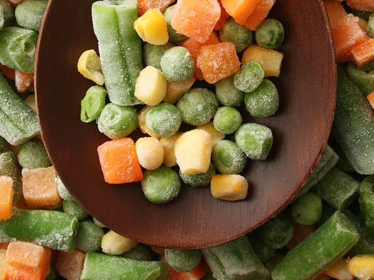 frozen peas, carrots and green beans on wooden spoon
