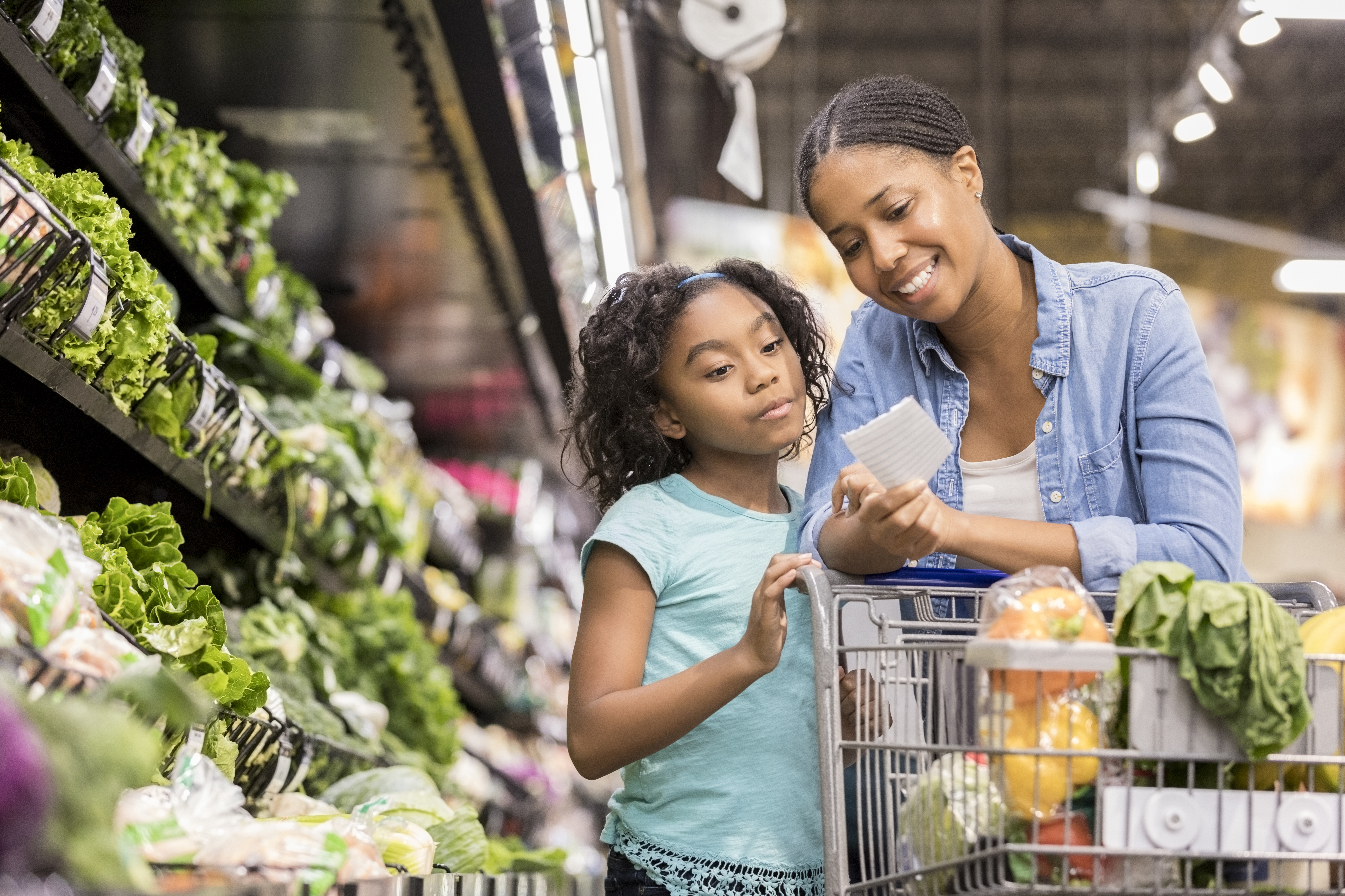 Mom and daughter looking at a grocery list in the produce section