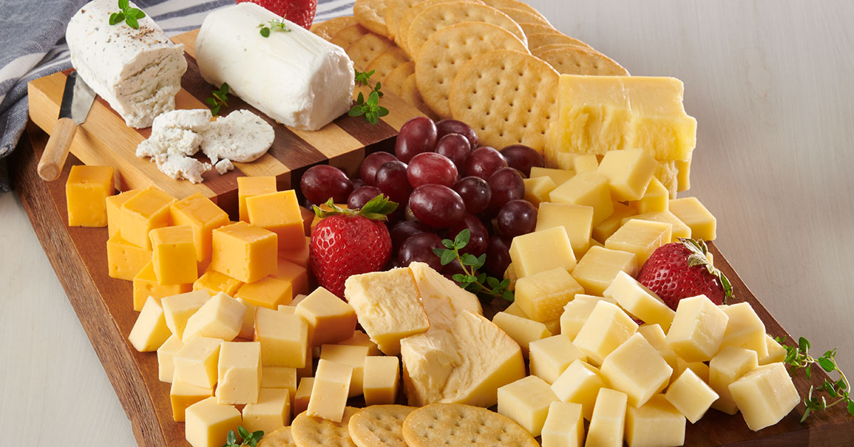 selection of gourmet cheeses with crackers on cutting board