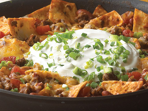 Skillet filled with nachos ground beef beans sour cream and scallions