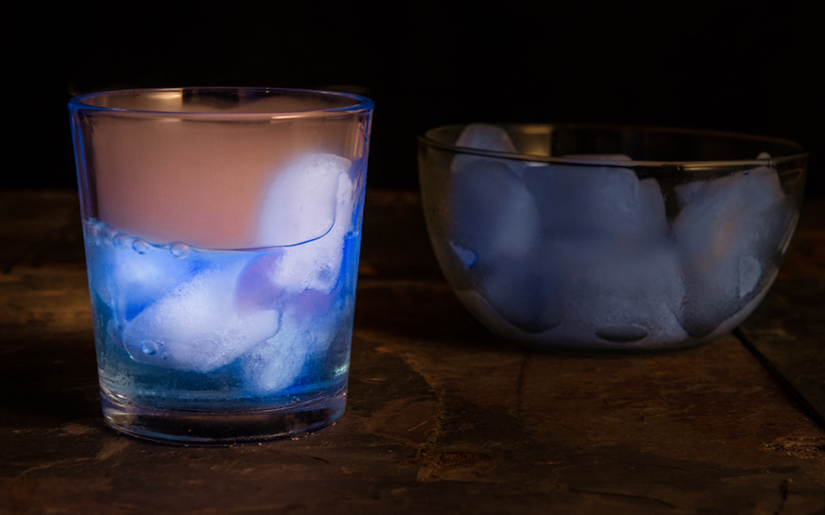 Drink containing Silver Tequila, Blue Curacao, grenadine syrup, Tonic water, ice cubes and Blacklights, for special effect
