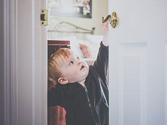 Toddler reaching for door handle