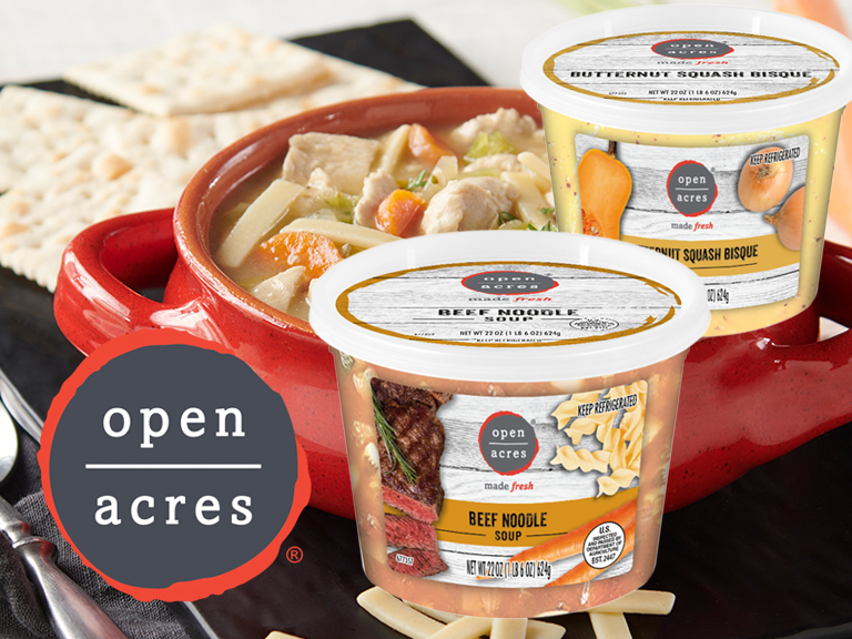 Open Acres brand soup containers with bowl of chicken noodle soup in background