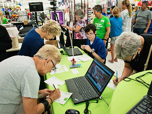 A crowd of shoppers sign up for grocery savings with teh YES Rewards Card.