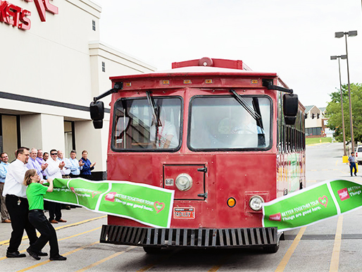 A trolley car brakes the ribbon at the Blair Family Fare Grand Opening Ceremony.